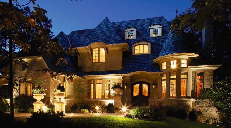 view of this house featuring timber high divided building, cottage, estate, evening, facade, historic house, home, house, landscape lighting, lighting, mansion, property, real estate, residential area, sky, villa, black, blue