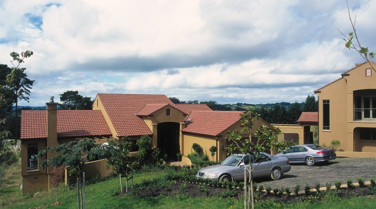 View of large home with terracotta coloured cladding area, cloud, cottage, estate, farm, farmhouse, home, house, land lot, landscape, neighbourhood, plant, property, real estate, residential area, roof, rural area, sky, suburb, tree, village, yard, white