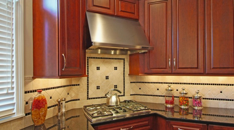 View of this kitchen designed and manufactured by cabinetry, countertop, cuisine classique, flooring, hardwood, home, interior design, kitchen, room, under cabinet lighting, wood stain, brown, red