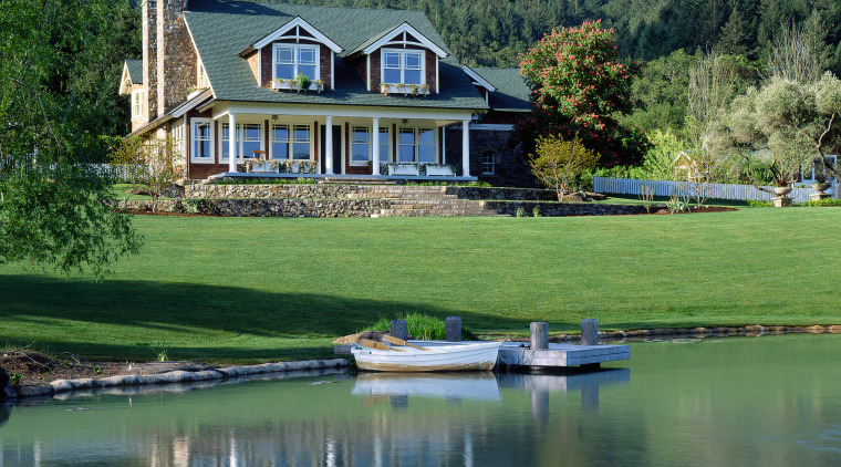 An exterior view of this traditional masonry home bank, canal, cottage, estate, farmhouse, home, house, lake, landscape, pond, property, real estate, reflection, reservoir, tree, water, waterway, green