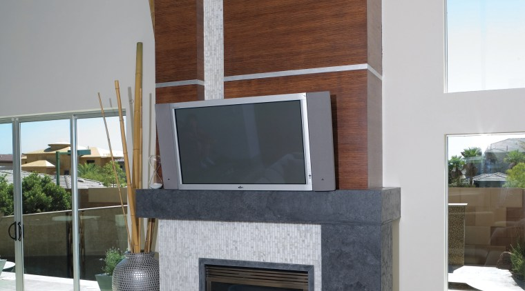The fireplace surround features pre-cast GFRC cast stone fireplace, hearth, interior design, living room, gray