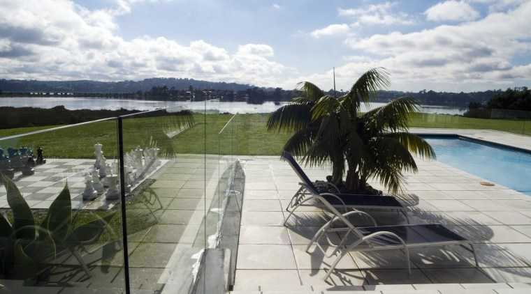 A view of this outdoor pool area featuring leisure, outdoor structure, property, real estate, sky, swimming pool, water, white