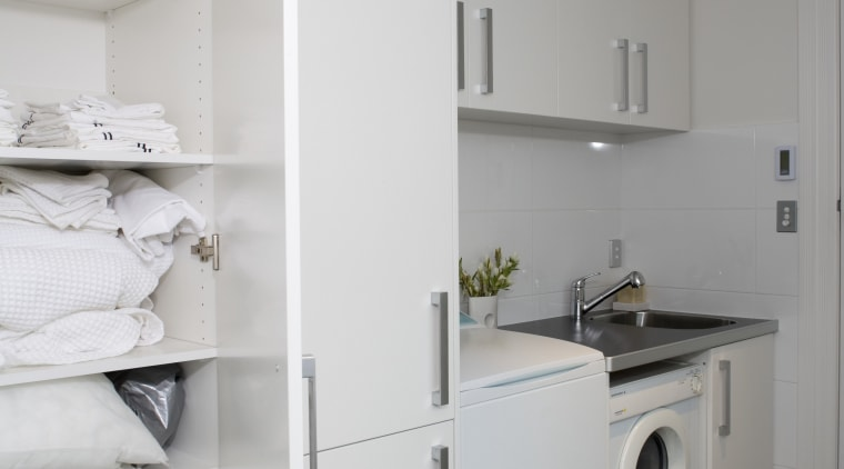 Tall cabinetry provides plenty of storage space. The floor, home, home appliance, interior design, kitchen, laundry, laundry room, major appliance, room, gray