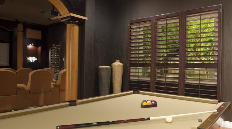 A view of the interior living areas featuring billiard room, billiard table, english billiards, games, indoor games and sports, interior design, pool, recreation room, room, table, wood, brown, black