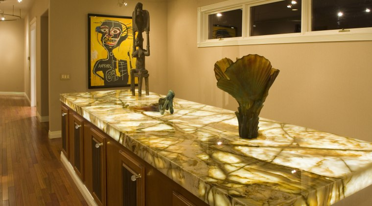 A view of artistic lighting showing the large countertop, flooring, interior design, kitchen, room, table, brown, orange