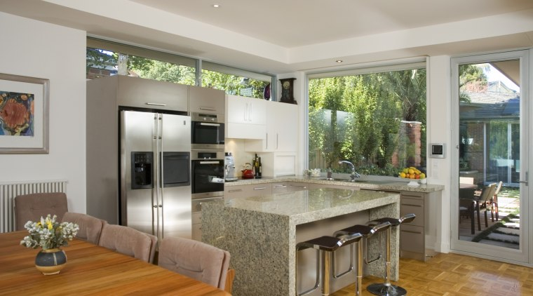 Several rooms, including the kitchen, connect to an countertop, interior design, kitchen, living room, real estate, window, gray, brown