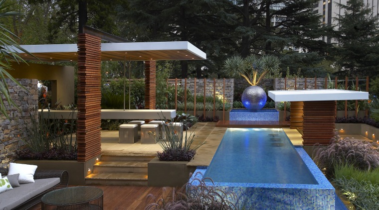 This contemporary landscape provides a series of interconnected backyard, estate, home, house, landscaping, lighting, outdoor structure, patio, property, real estate, swimming pool, yard, black, brown