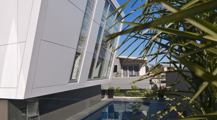 Image of a residential minimalist pool constructed by architecture, building, daylighting, daytime, facade, house, reflection, sky, swimming pool, water, black