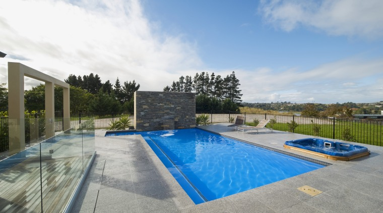 This new L-shaped pool, designed and built by estate, home, house, leisure, property, real estate, residential area, sky, swimming pool, villa, water, gray, teal