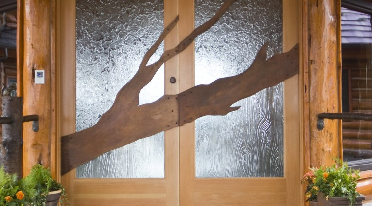 Image of unique designs on glass doors created door, floor, flooring, hardwood, home, house, interior design, outdoor structure, porch, real estate, wall, window, wood, wood stain, brown