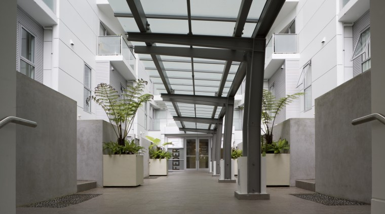 View of a two-storey maisonette which lines the building, condominium, courtyard, daylighting, lobby, gray