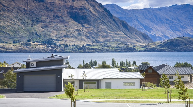 Exterior view of a home which features solar alps, cottage, elevation, estate, fjord, highland, home, house, lake, landscape, mountain, mountain range, property, real estate, residential area, roof, sky, suburb, tree, white