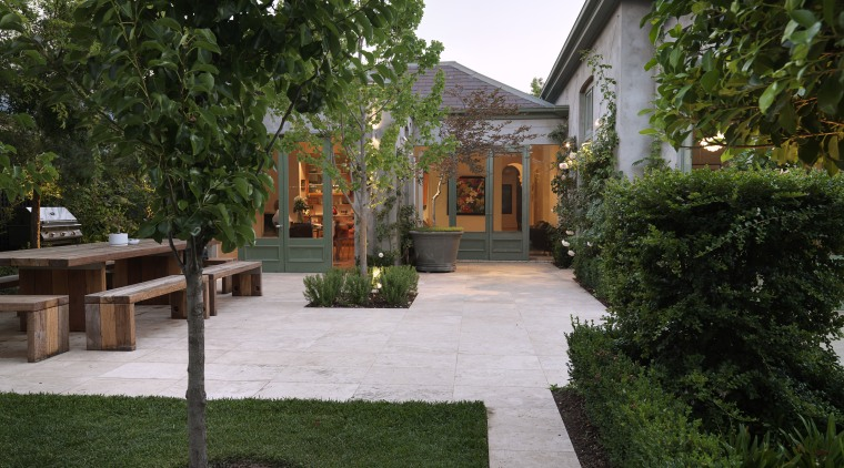 Exterior view of a villa featuring French doors backyard, cottage, courtyard, estate, garden, grass, home, house, landscape, landscaping, outdoor structure, property, real estate, walkway, yard, green, brown