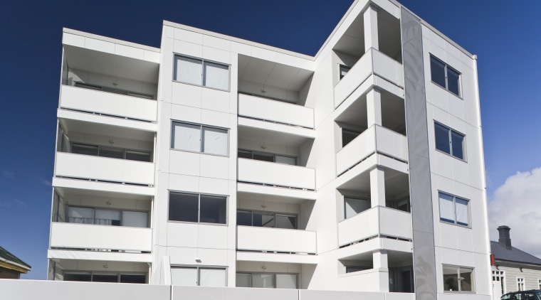 Exterior view of the Ivory apartments which features apartment, architecture, building, commercial building, condominium, corporate headquarters, elevation, facade, home, house, mixed use, property, real estate, residential area, white, blue