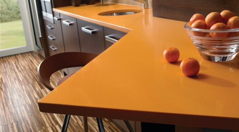 view of a kitchen which features an orange chair, countertop, floor, flooring, furniture, hardwood, interior design, kitchen, laminate flooring, room, table, wood, wood flooring, wood stain, brown, orange