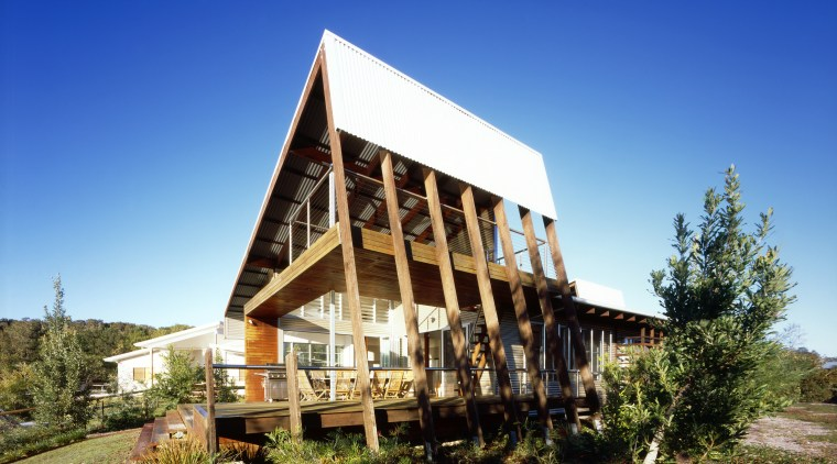Exterior view of a canal-side beach house which architecture, cottage, estate, farmhouse, home, house, property, real estate, sky, blue