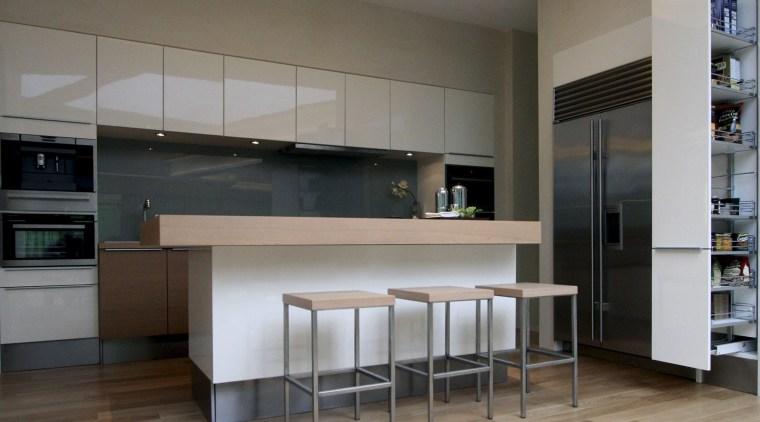 View of open-plan kitchen area featuring island woodgrain cabinetry, ceiling, countertop, floor, flooring, hardwood, interior design, kitchen, laminate flooring, room, wood, wood flooring, gray