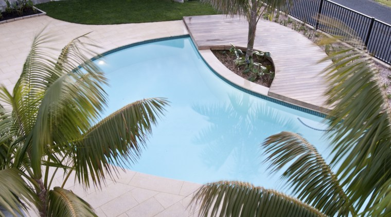 View of a resort-styled pool which was built arecales, backyard, estate, house, leisure, palm tree, plant, property, real estate, reflection, resort, swimming pool, vacation, water, gray