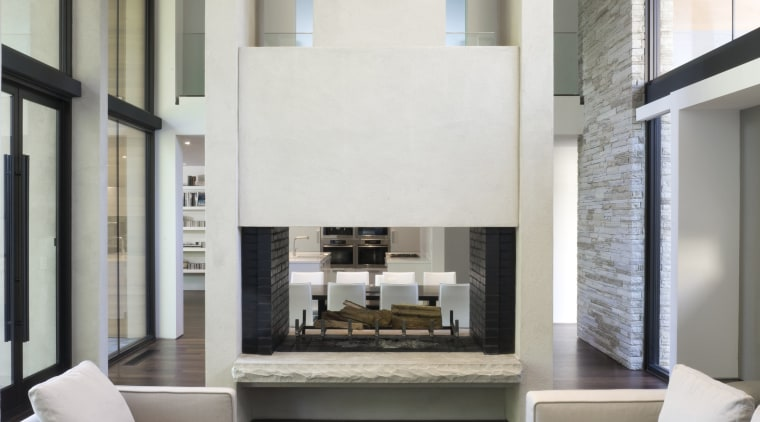 View of living area featuring double story fireplace, architecture, ceiling, floor, furniture, house, interior design, living room, table, white, gray