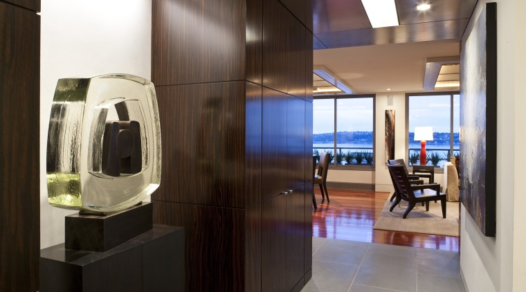 View of condominium entrance featuring wood wall paneling, interior design, room, brown