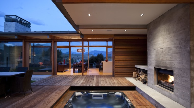 View of spa area with outdoor fireplace and architecture, estate, home, house, interior design, lighting, living room, real estate, swimming pool, window, wood, brown