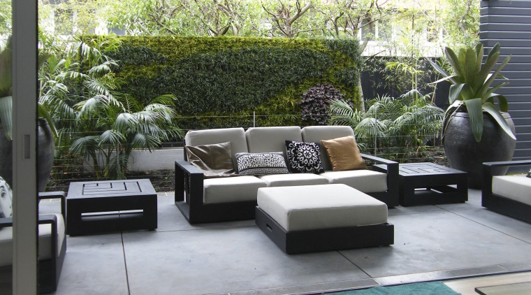 View of outdoor living space filled with mature floor, furniture, house, interior design, living room, outdoor structure, patio, property, real estate, gray