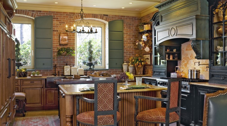 View of a traditional European-styled kitchen which features cabinetry, countertop, cuisine classique, dining room, estate, home, interior design, kitchen, living room, real estate, room, wood, brown