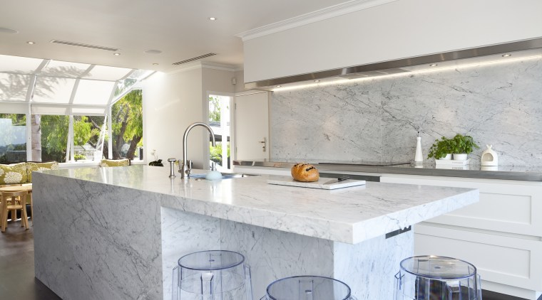 Carrara marble is used to create a centerpiece architecture, ceiling, countertop, floor, home, house, interior design, kitchen, real estate, room, table, gray, white