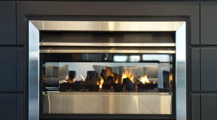 View of dark-toned indoor fireplace. black