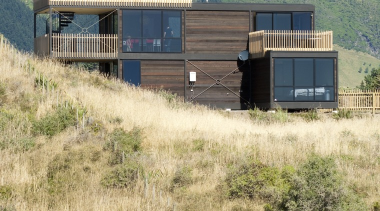 View of contemporary home on tussocky slope. architecture, home, house, land lot, landscape, prairie, property, real estate, rural area, shack, shed, sky, orange