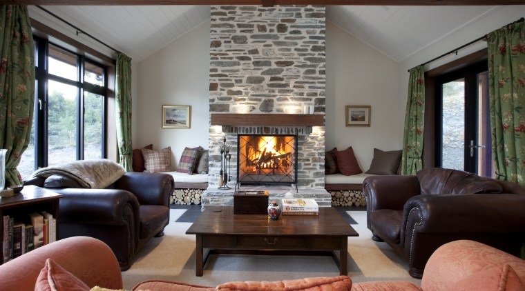 Lounge with brown leather chairs and stone chimney. home, interior design, living room, property, real estate, room, red, gray