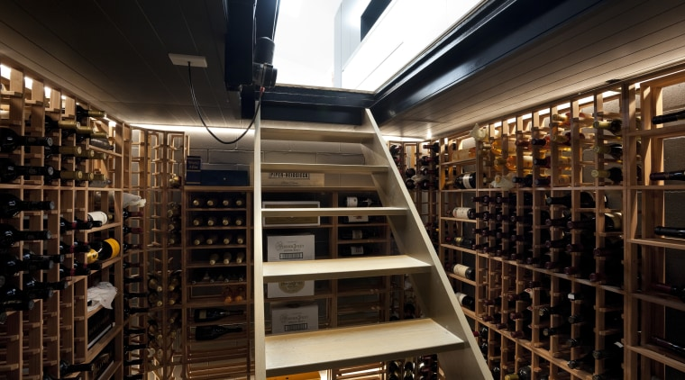 This fully lined basement wine cellar is accessed library, liquor store, wine cellar, winery, black