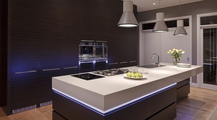 View of contemporary kitchen with brown wall, brown cabinetry, countertop, interior design, kitchen, room, under cabinet lighting, black