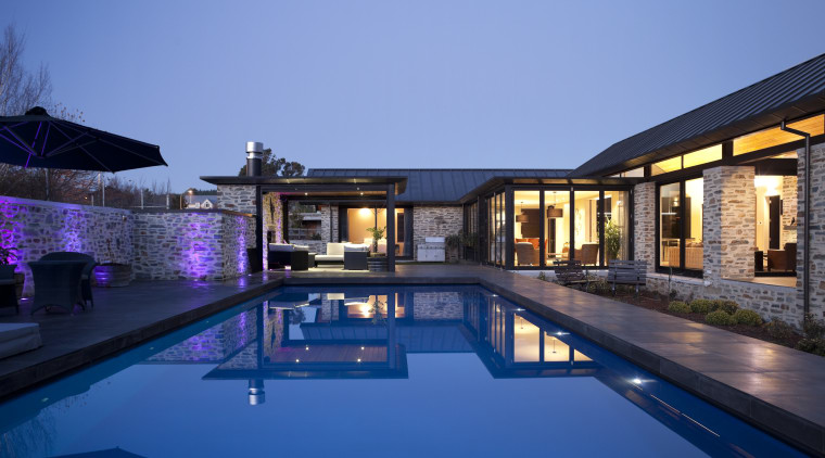 Night view of house from poolside. architecture, estate, home, house, leisure, lighting, mansion, property, real estate, reflection, residential area, resort, resort town, sky, swimming pool, villa, blue, teal
