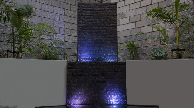 This water feature at night turns a bland, light, reflection, wall, gray, black