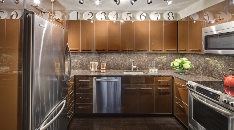 A row of decorative plates enliven the top cabinetry, ceiling, countertop, cuisine classique, interior design, kitchen, real estate, room, under cabinet lighting, brown, gray, black