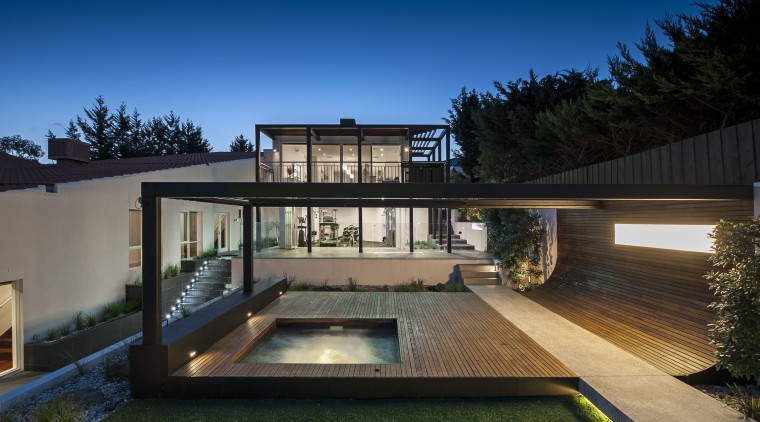 An exposed concrete pathway runs through the spotted architecture, backyard, cottage, daylighting, estate, facade, home, house, lighting, property, real estate, residential area, roof, siding, swimming pool, villa, window, black