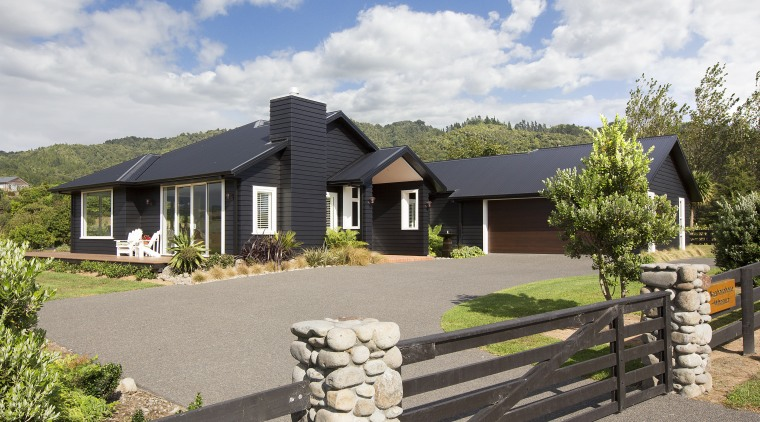 With its black weatherboards, sofites and roof this cottage, elevation, estate, facade, farmhouse, home, house, land lot, landscape, property, real estate, residential area, gray, white