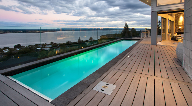 This modern lap pool forms the centrepiece of deck, estate, leisure, property, real estate, roof, sky, swimming pool, water, gray