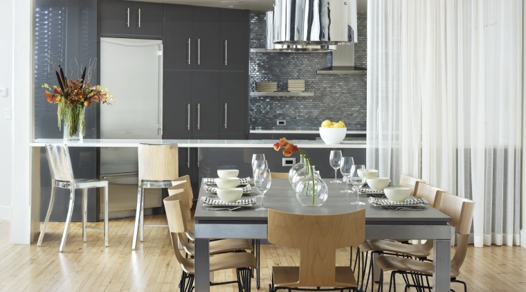 High-gloss gray cabinets and metallic glass tiles define chair, dining room, floor, flooring, furniture, interior design, kitchen, living room, room, table, wall, wood flooring, white, gray