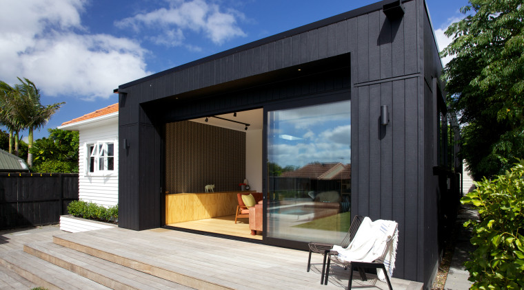 A deep soffit provides some shade on the architecture, backyard, cottage, facade, home, house, real estate, shed, siding, black, gray