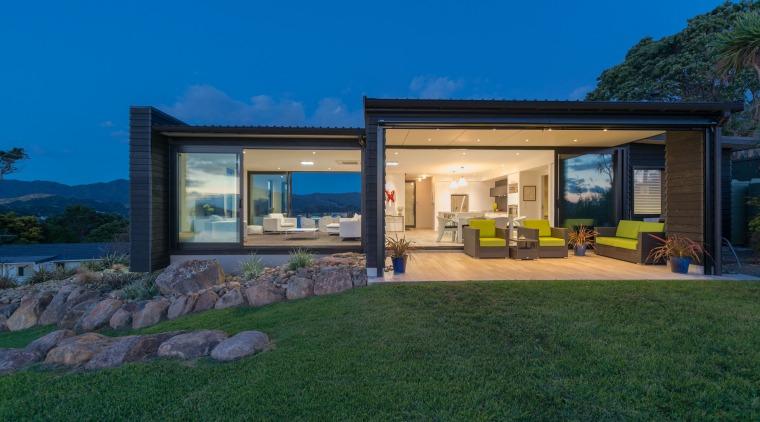 A large overhang creates a sheltered outdoor living architecture, backyard, cottage, estate, facade, home, house, landscape, property, real estate, sky, villa, window, yard, blue