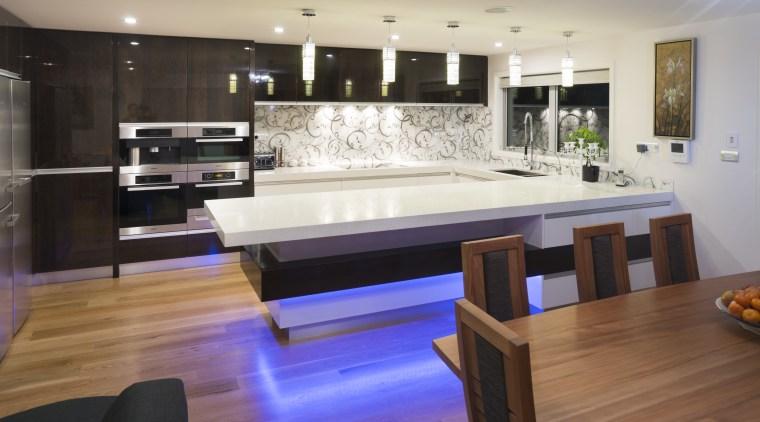 Dark wood veneer contrasts white lacquered cabinetry in countertop, floor, flooring, hardwood, interior design, kitchen, room, table, wood, wood flooring, gray
