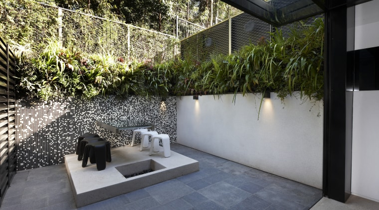 This new terrace house has a black and architecture, backyard, courtyard, garden, home, house, outdoor structure, plant, property, real estate, wall, yard, gray, black