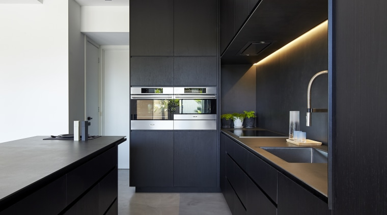 Two Askö wall ovens anchor the side wall architecture, cabinetry, ceiling, countertop, house, interior design, interior designer, kitchen, black, white