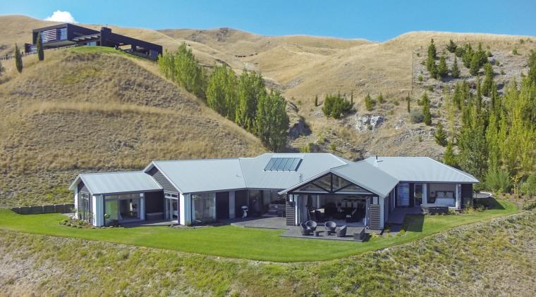 This custom-designed home by GJ Gardner Homes features cottage, estate, farm, farmhouse, grassland, highland, hill, home, house, hut, land lot, landscape, property, real estate, rural area, brown