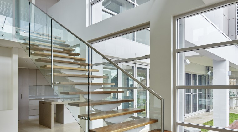 Soaring double-height voids create a light, airy interior architecture, condominium, daylighting, estate, floor, glass, handrail, home, house, interior design, real estate, stairs, gray