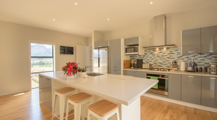 This well-insulated single-storey home constructed by Evolution has countertop, cuisine classique, floor, flooring, interior design, kitchen, property, real estate, room, orange