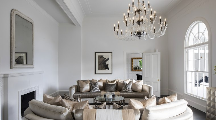 A large chandelier is the centrepiece of this ceiling, estate, furniture, home, interior design, living room, room, table, gray