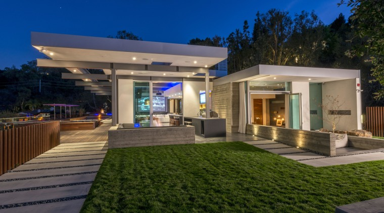The board-formed concrete wall seen behind the barbecue architecture, backyard, elevation, estate, facade, home, house, lighting, property, real estate, residential area, roof, villa, brown